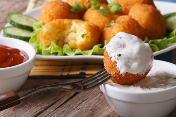 Fried potato balls with sour cream close-up horizontal.