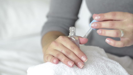 Woman applies clear varnish nail polish to her nails manicure