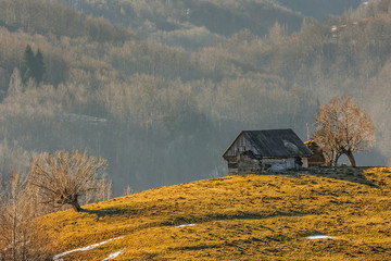 Old wooden hut at sunny dawn, Pestera village, Romania
