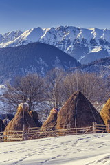Mountain landscape with farm and haystacks in winter, Romania