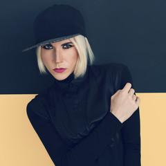 Stylish blonde in black cap and black shirt. Latest fashion tren