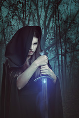 Beautiful woman with magic sword in a dark forest
