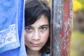 Young girl with expressive eyes, close-up portrait outdoors.
