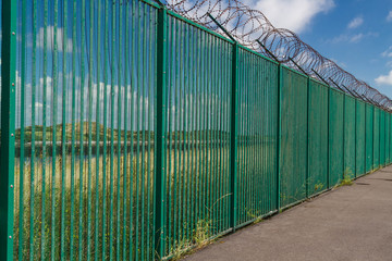Razor wire on top of green fence guarding French ferry terminal.