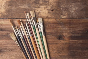 Set of paintbrushes on a wood background, tinted photo