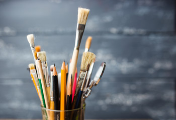 Photo of paint brushes in a glass standing on old wooden table,