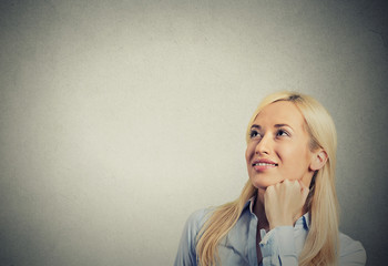 happy woman thinking looking up isolated grey wall background