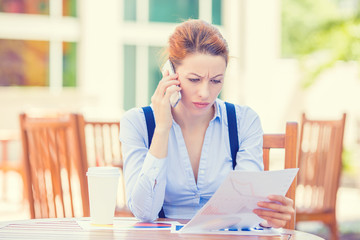 unhappy serious woman talking on phone looking at documents