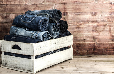 Old  jeans in wooden box over grungy background