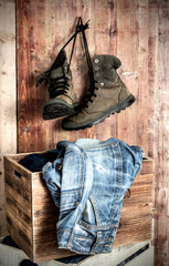 Old Boots and jeans over wooden background