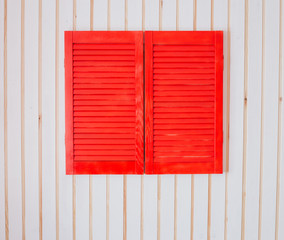 Red wooden shutters on a white wall