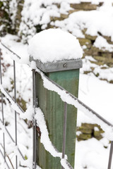Snow on wooden pole and fence