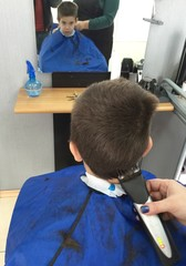 Child in hairdressing salon. Hair cutting