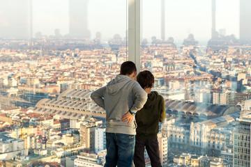 Due bambini guardano la città dalla finestra di un grattacielo