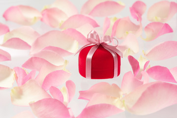 Background with small red velvet ring box and rose petals