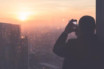 Uomo che fotografa il tramonto dall'alto