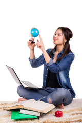 girl sitting on the carpet with a globe, a laptop and books