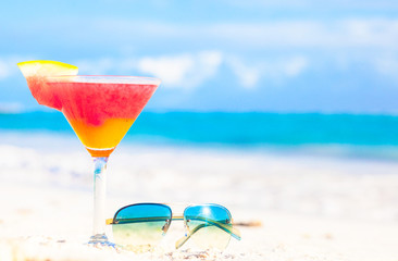 glass of chilled cocktail rum punch and sunglasses on table near
