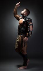 Image of handsome dancer posing as primitive man