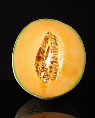 Half of cantaloupe melon fruit with reflection isolated