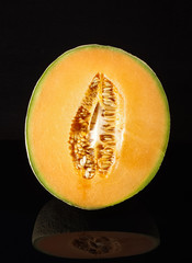 Cantaloupe melon fruit on black reflective surface isolated