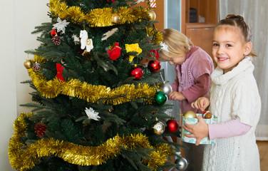 Little girls decorating Christmas tree
