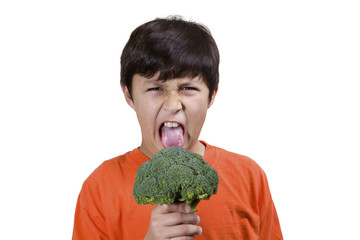 Young boy frowns while holding broccoli on white background