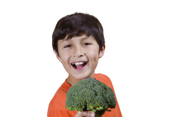 Young boy smiles while holding broccoli on white background