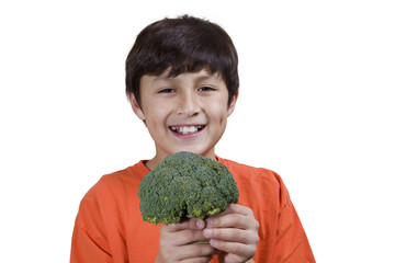 Young boy holding broccoli