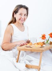 older woman having breakfast in   bedroom