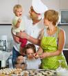 Happy family of four making  dumplings