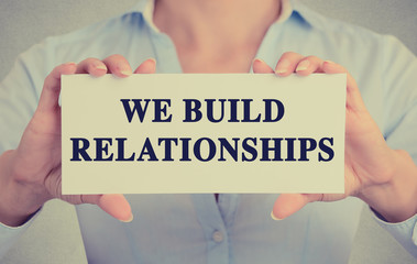 businesswoman hands holding card we build relationships message