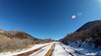 POV vehicle road drive snow rock blue sky extreme terrain Zion National Park Utah