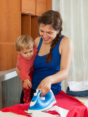 Housewife with baby  ironing clothes
