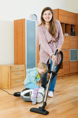 Mother with baby cleaning living room