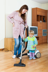 Mother with baby cleaning  home