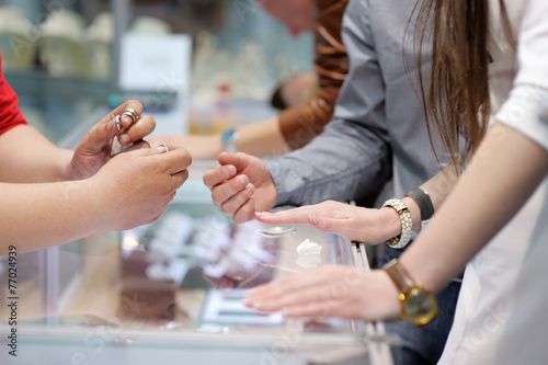 Woman trying wedding rings at a jeweler - 77024939