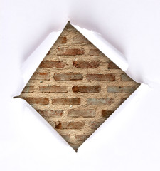 Brick wall background through torn paper