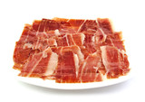 Serrano ham slices on a white dish. Jabugo. Spanish tapa.