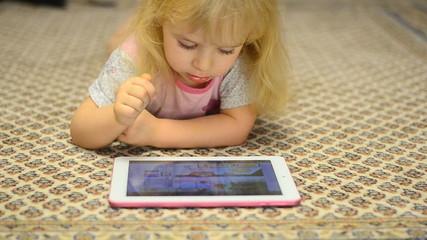 Cute Little Girl Works on Tablet Computer Lying on Carpet
