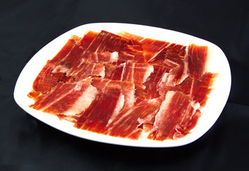 Serrano ham slices on a white dish over black wackground. Jabugo