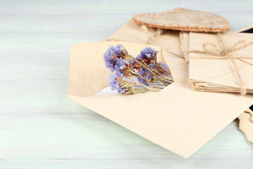 Old letters with dry flowers on wooden background