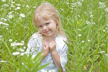 little blond girl in a wild daisy field