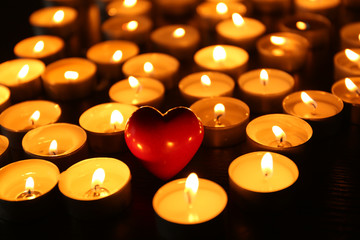 Burning candles with heart on dark background