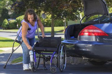 Woman with Spina Bifida dismantling wheelchair for transport