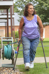 Woman with Spina Bifida walking with crutches and garden hose