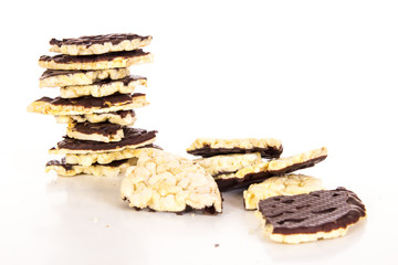 Pieces of chocolate coated rice cakes on white background