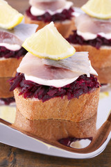 Rye toasts with herring and beets on metal tray close up