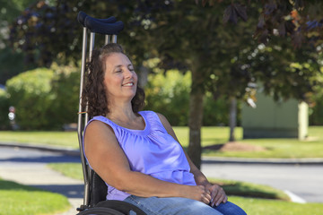 Woman with Spina Bifida relaxing in wheelchair with crutches