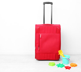 Red suitcase with child toys  isolated on white